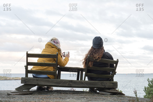 Sweden, Sodermanland, Braviken, Rear view of teenage girl and young woman sitting on wooden chairs by lake and taking pictures