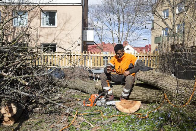 Sweden, Sodermanland, Arborist sitting on log
