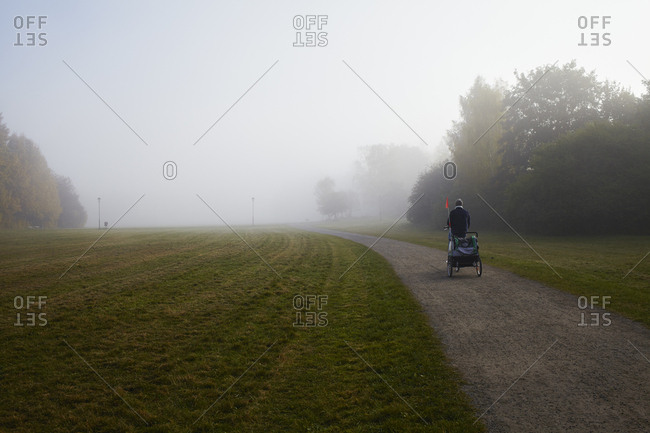 Sweden, Sodermanland, Johanneshov, Nytorps garde, Person cycling on dirt road in fog
