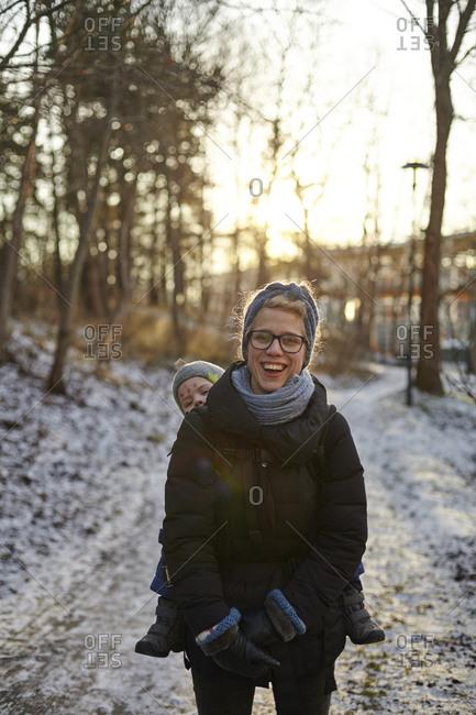 Sweden, Sodermanland, Stockholm, Johanneshov, Hammarbyhojden, Laughing mid adult woman carrying son