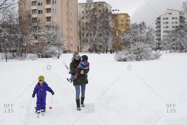 Sweden, Sodermanland, Stockholm, Johanneshov, Mid adult woman walking with children