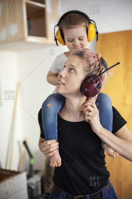Sweden, Mid adult woman carpenter carrying son on shoulders