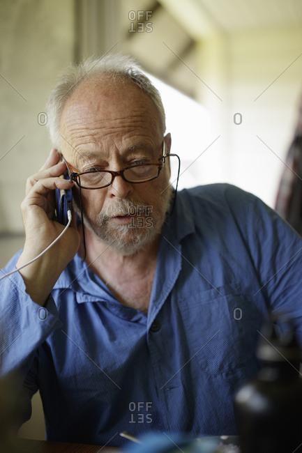 Sweden, Senior man talking on phone