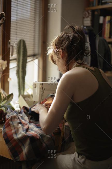 Sweden, Skane, Lund, mid adult woman working on sewing machine