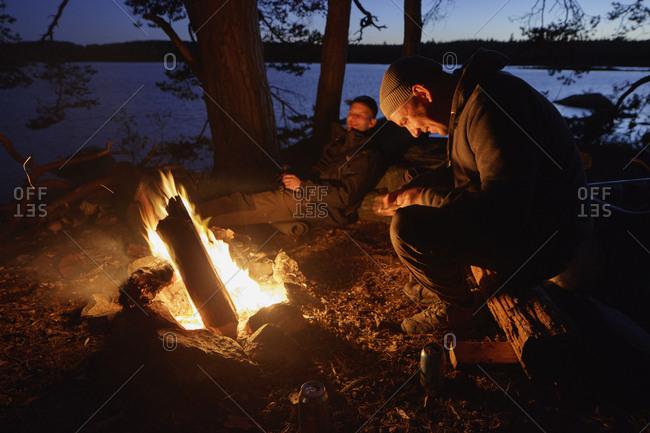 Sweden, Skane, Filkesjon, Mid adult men sitting around campfire at dusk