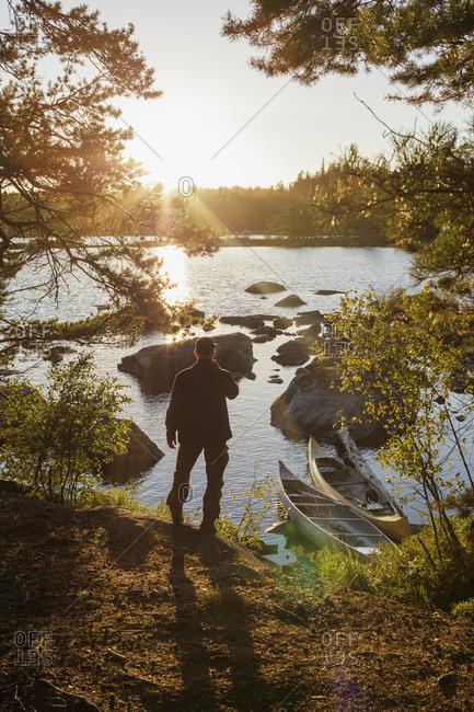 Sweden, Skane, Filkesjon, Rear view of man standing on shore and looking at lake