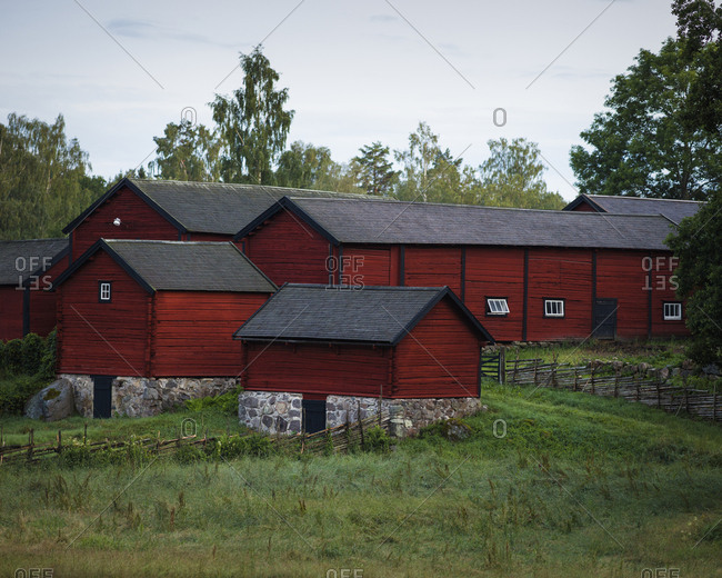 Sweden, Smaland, Stensjo, Grassy field and brown houses