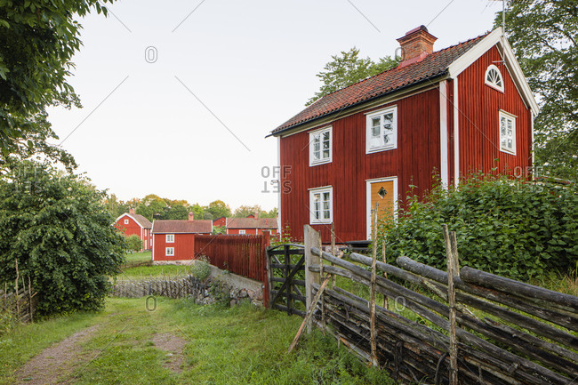 Sweden, Smaland, Stensjo, Traditional wooden fence and brown house