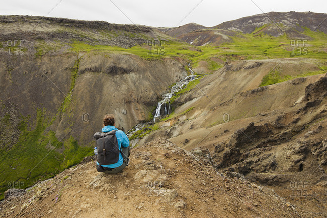 Iceland, Sudurland, Hveragerdi, Reykjadalur, Tourist looking at stream and waterfalls in rocky valley