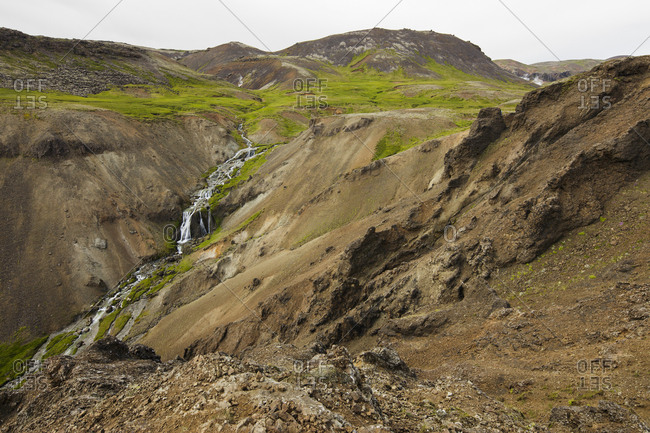 Iceland, Sudurland, Hveragerdi, Reykjadalur, Stream and waterfalls in rocky valley