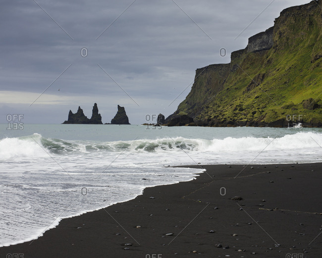 Iceland, Sudurland, Vik i Myrdal, Rock formations and black sand on beach at feet of cliff