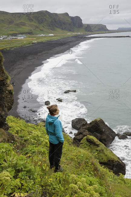 Iceland, Sudurland, Vik i Myrdal, Hiker looking from cliff at black sand beach