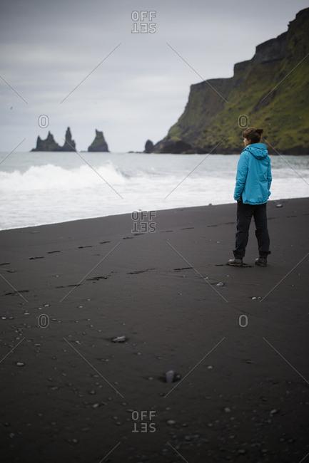 Iceland, Sudurland, Vik i Myrdal, Hiker standing on black sand beach at feet of cliff