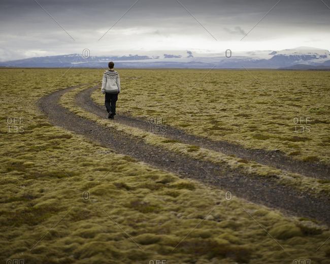 Iceland, Sudurland, Hiker on dirt road through wilderness towards mountain range on horizon