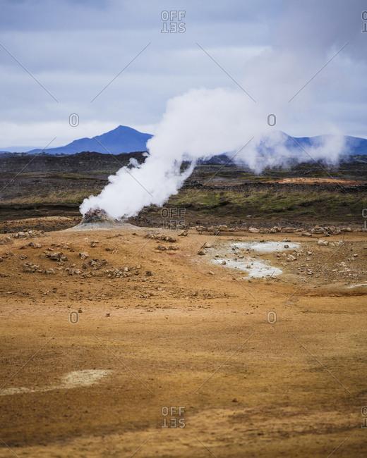Iceland, Nordurland eystra, Hverarond, Steam over hot springs with mountain range on horizon