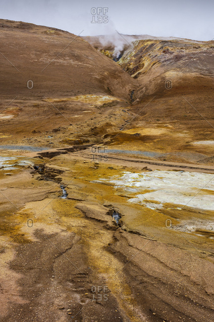 Iceland, Nordurland eystra, Hverarond, Steam over hot springs among rocky mountains
