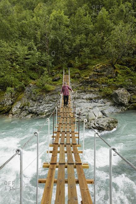 Norway, Jotunheimen, Utladalen, Man walking on suspension bridge over river