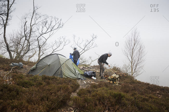 Sweden, Skane, Soderasen, Two men camping on grassy hill