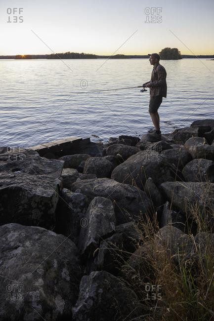 Sweden, Skane, Immeln, Man fishing in lake at sunset
