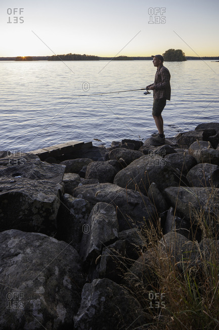 Sweden, Skane, Immeln, Man fishing in lake at sunset