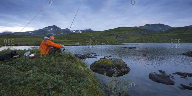 Norway, Troms, Sjuendevatnet, Man fishing in lake at dusk