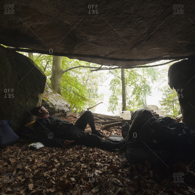 Sweden, Blekinge, Halen, Man lying down in cave