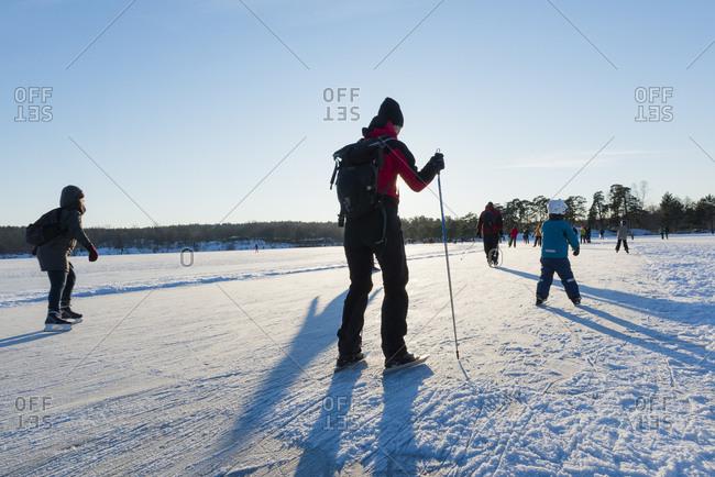 Sweden, Sodermanland, Nacka, Hellasgarden, People ice skating on sunny day