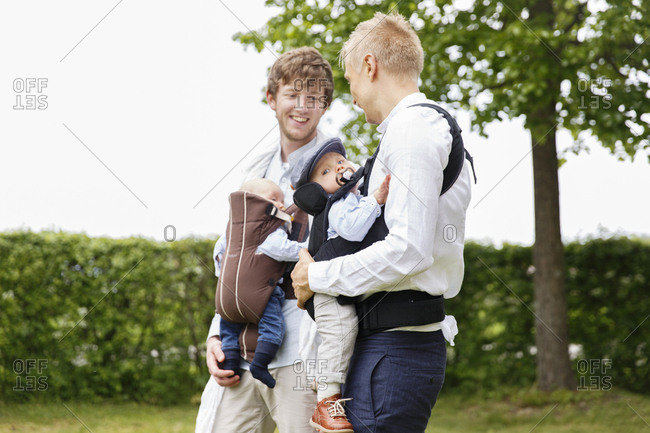 Sweden, Sodermanland, Two fathers holding baby boys in garden