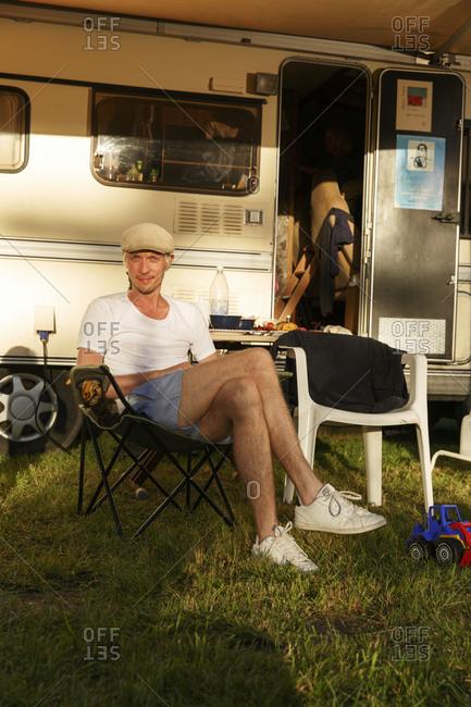 Sweden, Sodermanland, Trosa, Man sitting in front of trailer home