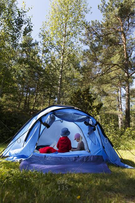 Sweden, Sodermanland, Trosa, Kids sitting in blue tent