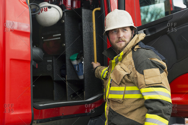 Sweden, Sodermanland, Firefighter standing in front of fire truck