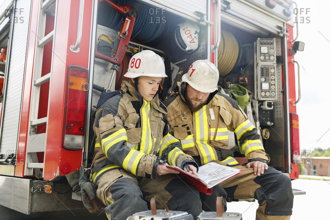 Sweden, Sodermanland, Firefighters studying documents