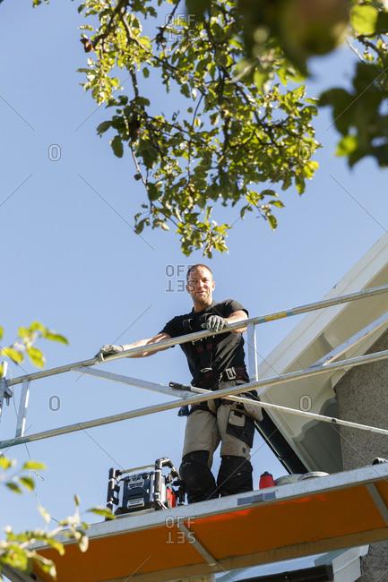 Sweden, Sodermanland, Jarna, Man standing on scaffold