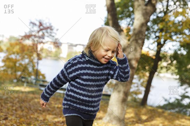 Sweden, Sodermanland, Stockholm, Sodermalm, Langholmen, Blonde boy laughing in autumn park
