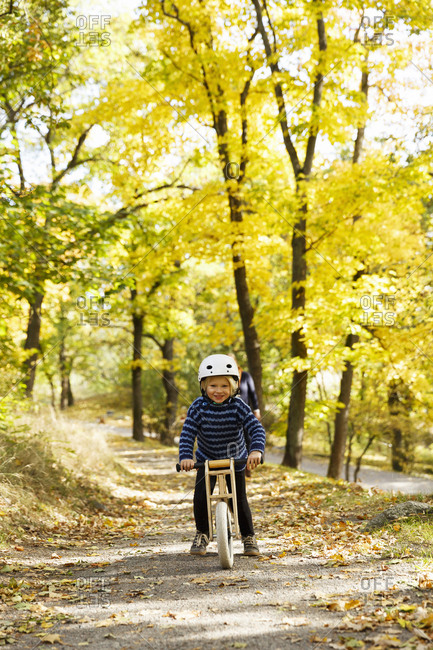 Sweden, Sodermanland, Stockholm, Sodermalm, Langholmen, Boy cycling in park in autumn