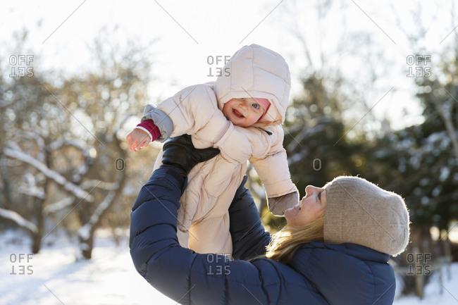 Sweden, Mother holding daughter aloft