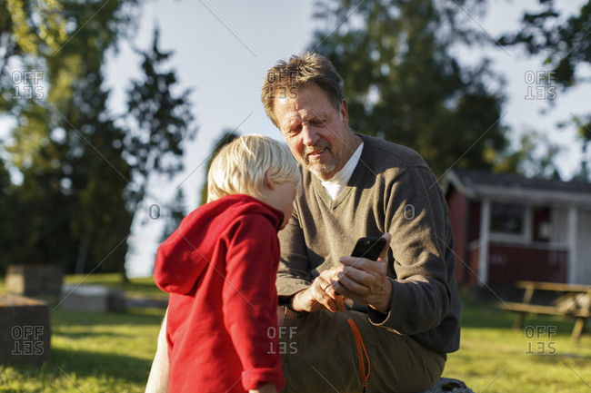Sweden, Sodermanland, Jarna, Grandfather using smart phone with grandson