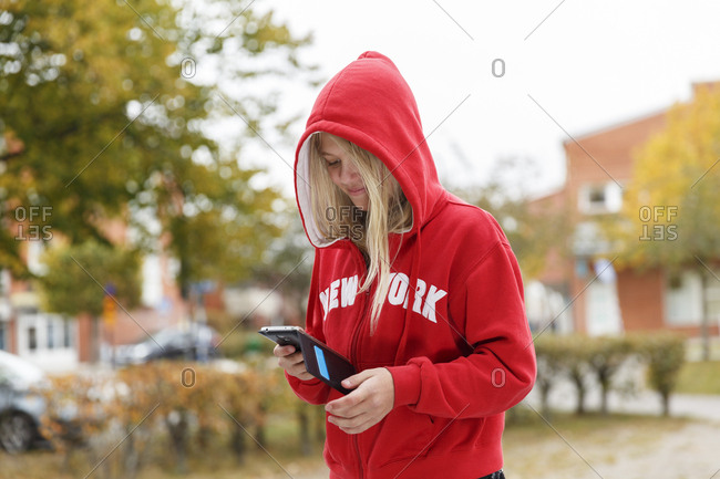 Sweden, Sodermanland, Jarna, Portrait of girl with hood on using smart phone