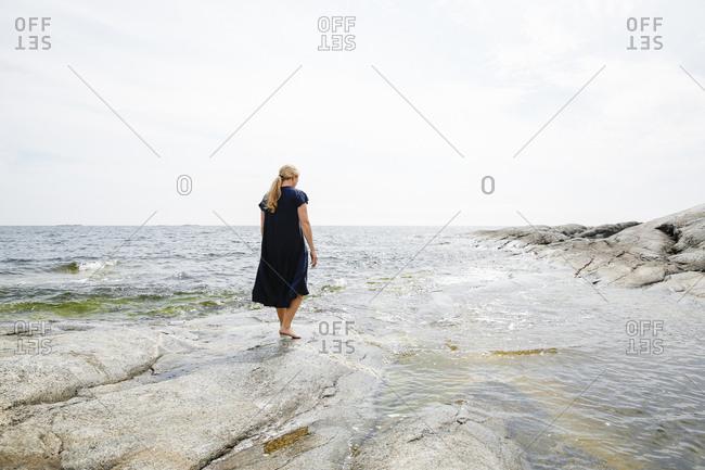 Sweden, Stockholm Archipelago, Sodermanland, Huvudskar, Rear view of mature woman wading in sea