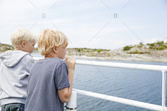 Sweden, Stockholm Archipelago, Sodermanland, Huvudskar, Two boys looking at lake