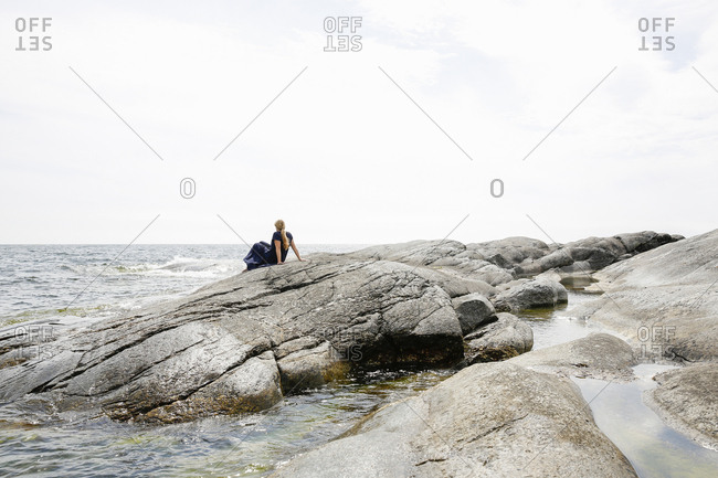Sweden, Stockholm Archipelago, Sodermanland, Huvudskar, Mature woman sitting on rocky seashore