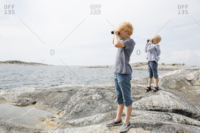 Sweden, Stockholm Archipelago, Sodermanland, Huvudskar, Two boys looking through binoculars on rocky seashore