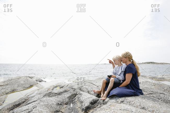Sweden, Stockholm Archipelago, Sodermanland, Huvudskar, Mother and son sitting on rocky seashore