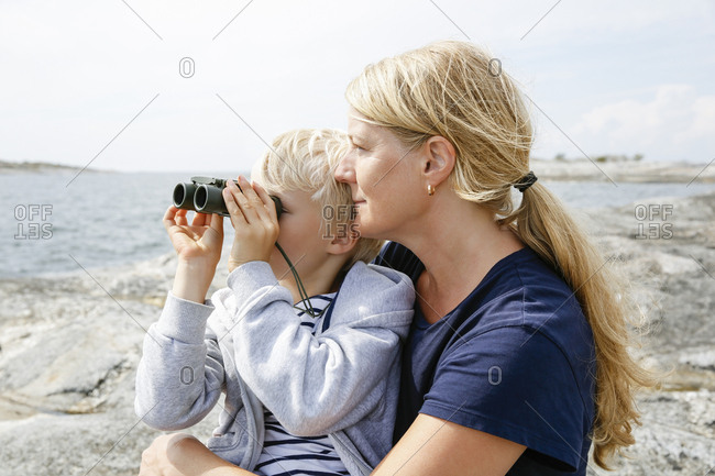 Sweden, Stockholm Archipelago, Sodermanland, Orno, Mother and son sitting on rocky seashore, son looking through binoculars