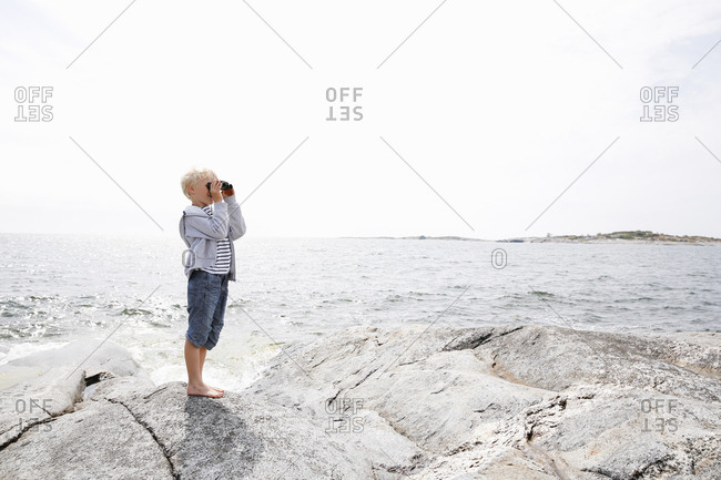 Sweden, Stockholm Archipelago, Sodermanland, Orno, Boy standing on rocky seashore and looking through binoculars