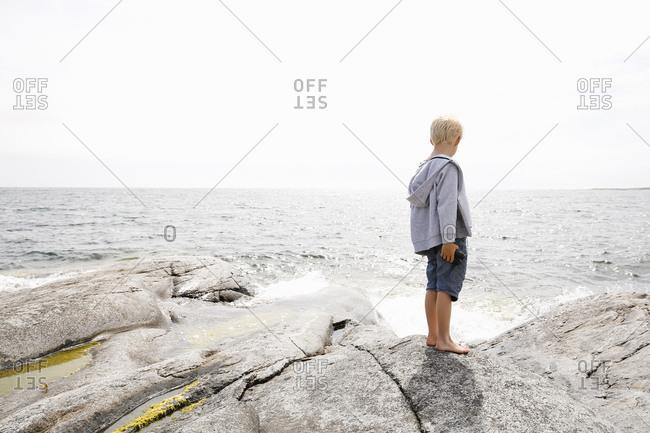Sweden, Stockholm Archipelago, Sodermanland, Orno, Boy standing on rocky seashore