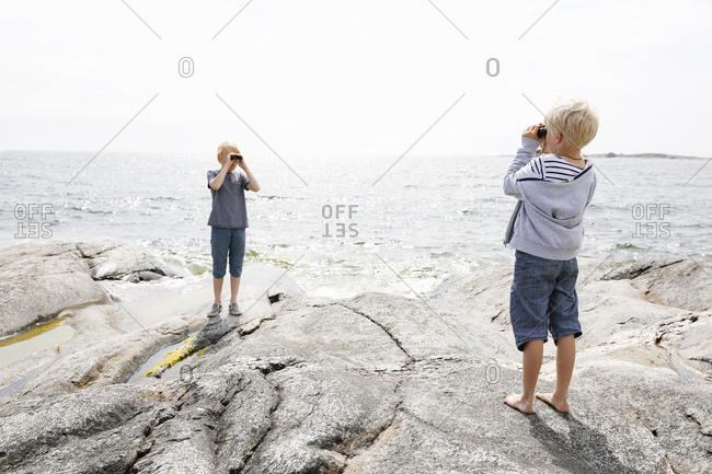Sweden, Stockholm Archipelago, Sodermanland, Orno, Two boys standing on rocky seashore and looking through binoculars
