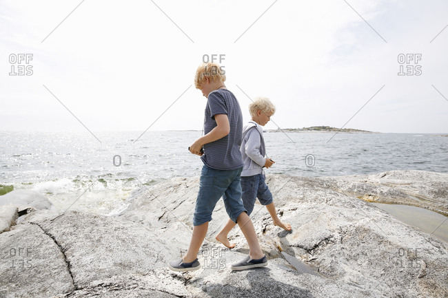 Sweden, Stockholm Archipelago, Sodermanland, Orno, Two boys walking on rocky seashore