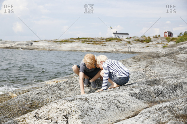 Sweden, Stockholm Archipelago, Sodermanland, Orno, Two boys playing on rocky seashore