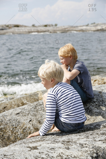 Sweden, Stockholm Archipelago, Sodermanland, Orno, Two boys sitting on rocky seashore